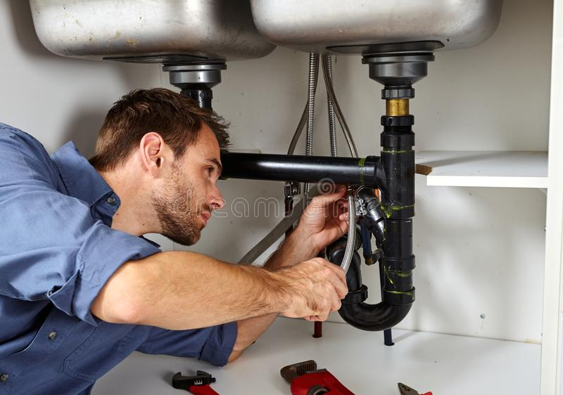 Plumber. Plumber with tools doing reparation in the kitchen stock images