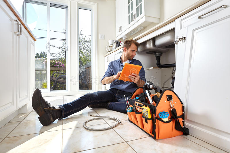 Plumber. Plumber with tools doing reparation in the kitchen royalty free stock photos