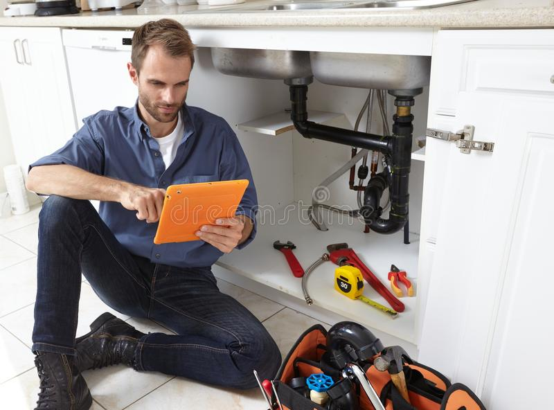 Plumber. Plumber with tools doing reparation in the kitchen royalty free stock photography