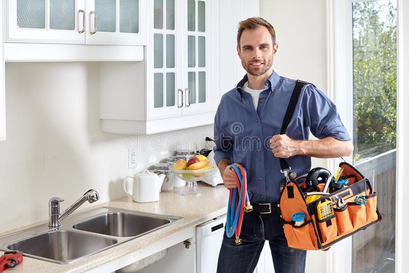 Plumber. Plumber with tools doing reparation in the kitchen stock photo
