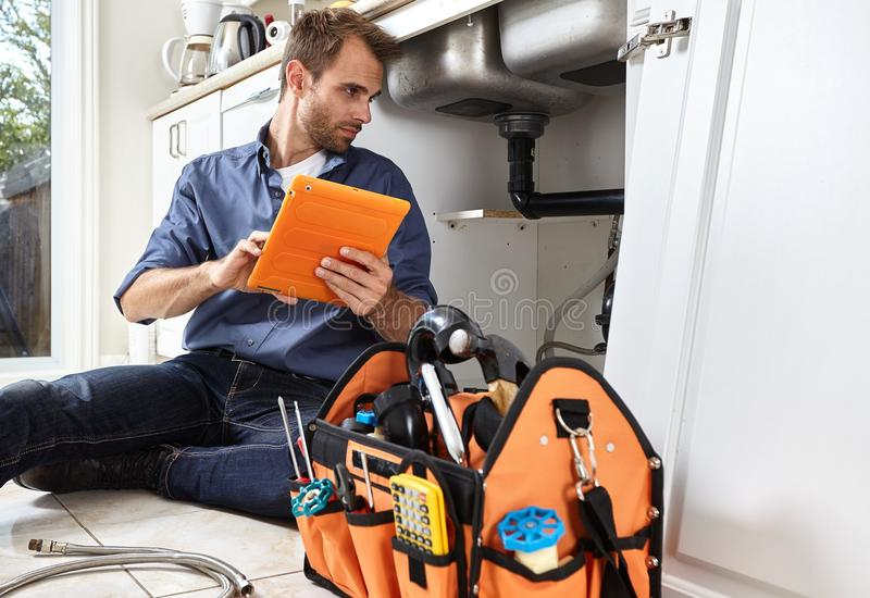 Plumber. Plumber with tools doing reparation in the kitchen royalty free stock image