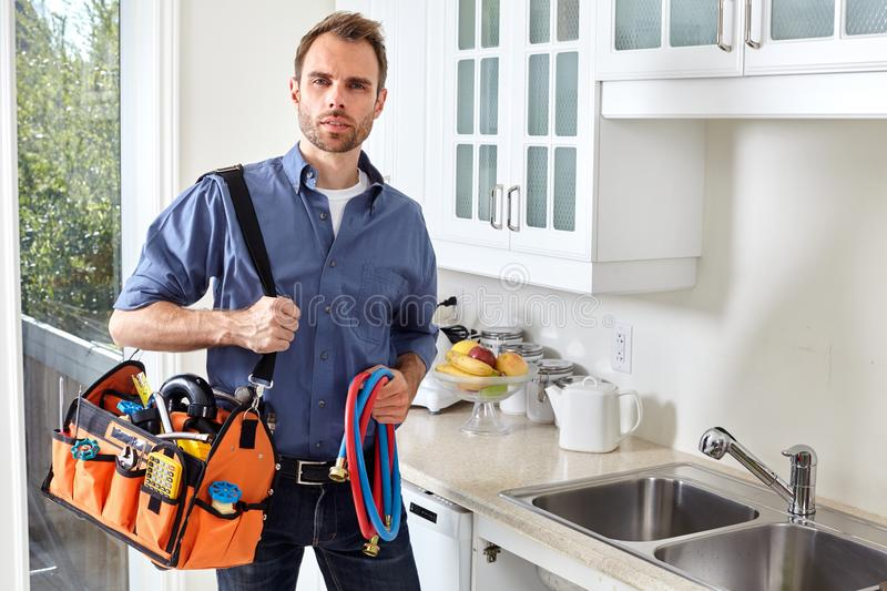 Plumber. Plumber with tools doing reparation in the kitchen stock photos