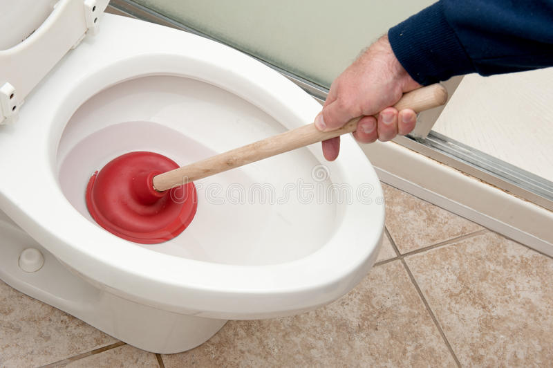 Plumber uncloging toilet. A plumber uses a plunger to unclog a toilet stock photos