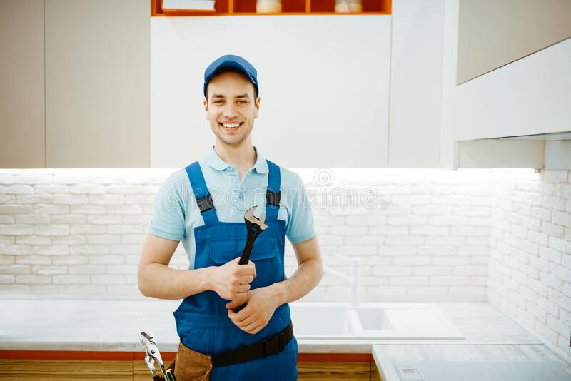 Plumber in uniform fixing faucet in the kitchen stock images