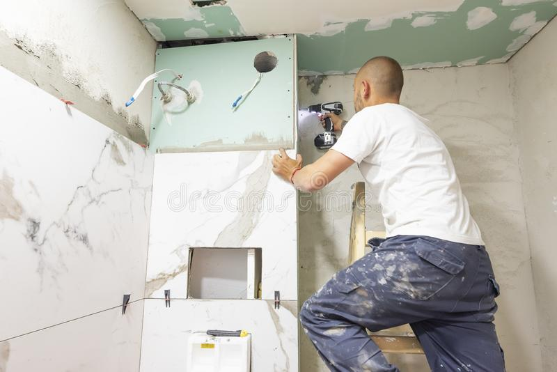 Plumber using electric screwdriver. Bathroom renovation concept. Marble ceramic tiles with spacers and grey cement walls in stock photography