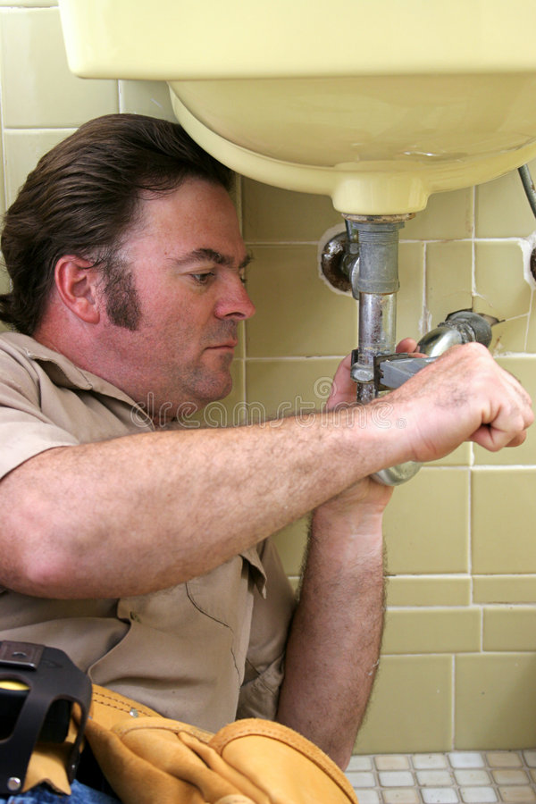 Plumber Using Pipe Wrench. A plumber using a pipe wrench to repair a sink stock photography