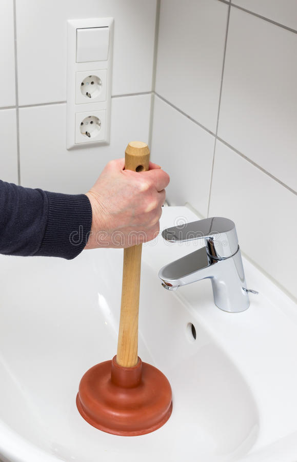 A Plumber Using Plunger In Bathroom Sink stock images