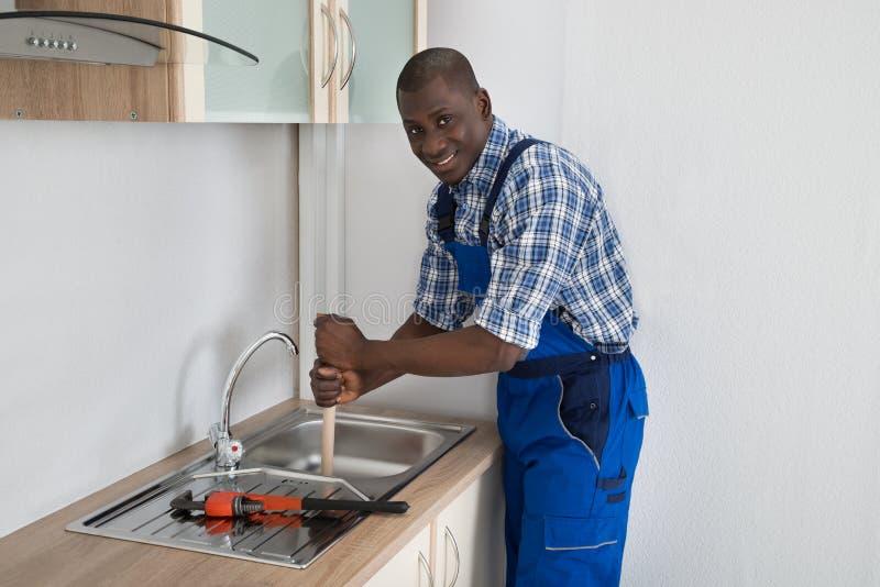 Plumber Using Plunger In Kitchen Sink royalty free stock image