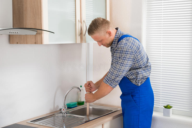 Plumber Using Plunger In Sink. Male Plumber Using Plunger In Stainless Steel Sink In Kitchen royalty free stock image
