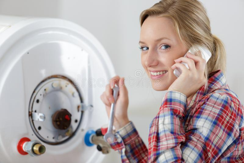 Plumber woman builder fixing boiler stock photos
