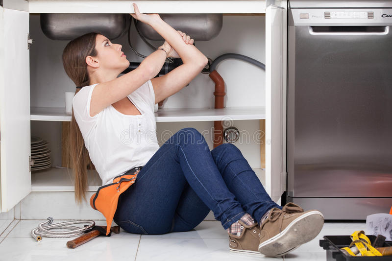 Plumber woman repairing de pipe of the kitchen royalty free stock photos