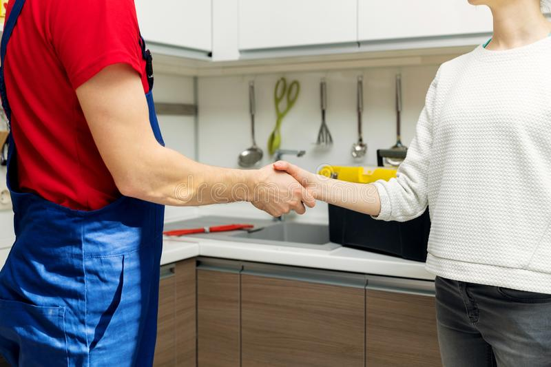 plumber and woman shaking hands after repairs stock photos