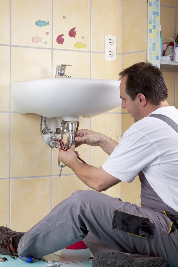 Plumber at work. Studio-shot of a plumber repairing the drain of a sink and changing a clogged siphon royalty free stock photography