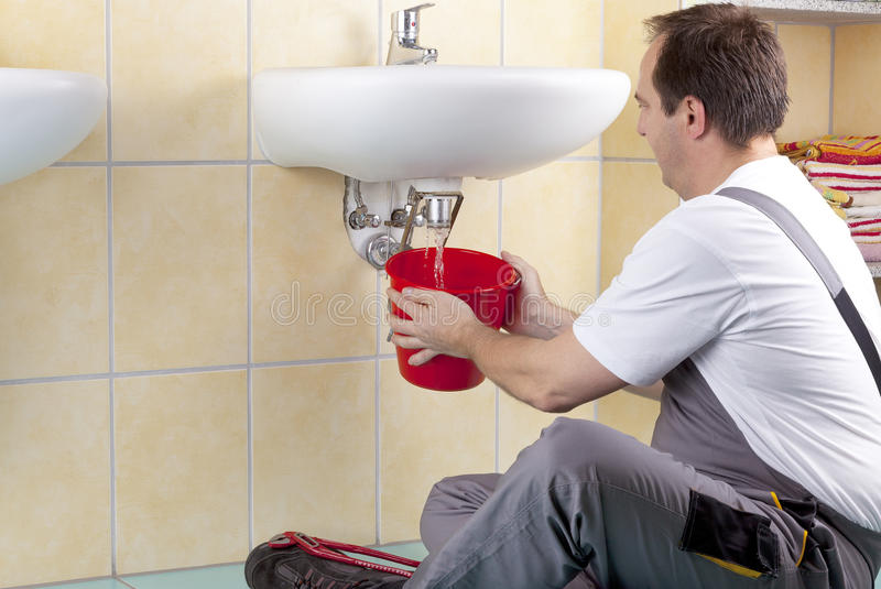 Plumber at work. Studio-shot of a plumber repairing the drain of a sink and changing a clogged pipe. the plumber is flushing the drain royalty free stock photos