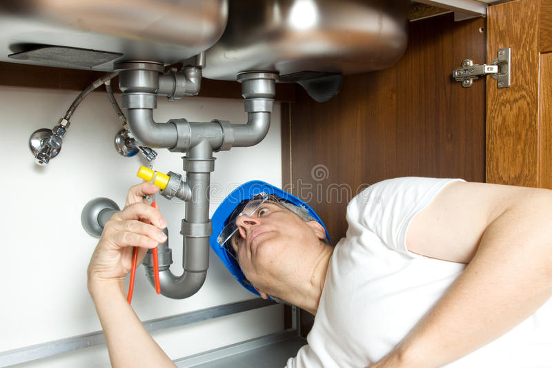 Plumber at work. With the pipes of a kitchen royalty free stock image
