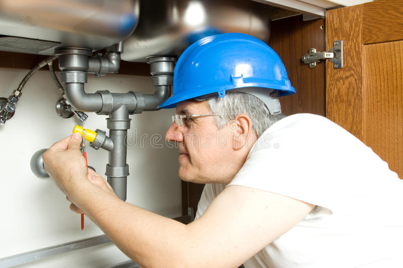 Plumber at work. With the pipes of a kitchen stock photos