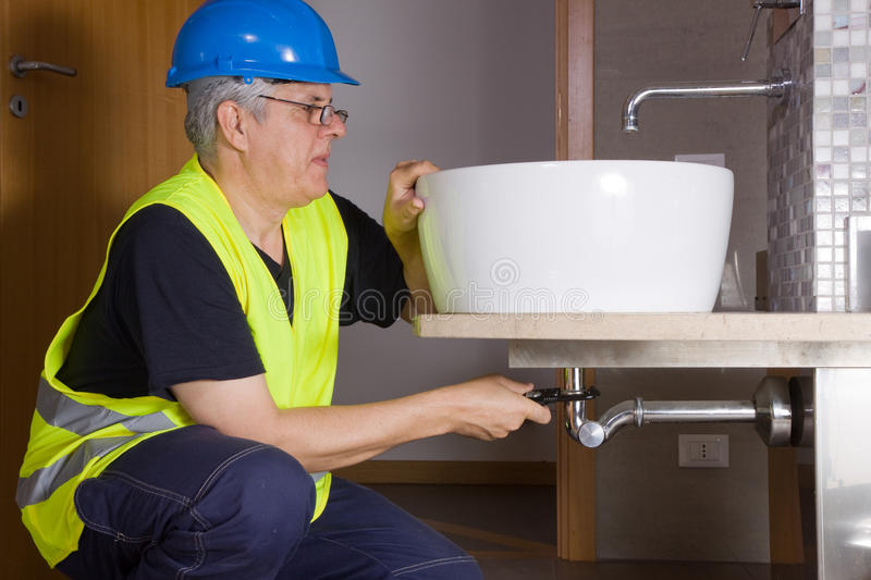 Plumber at work. With a basing in a bathroom stock image