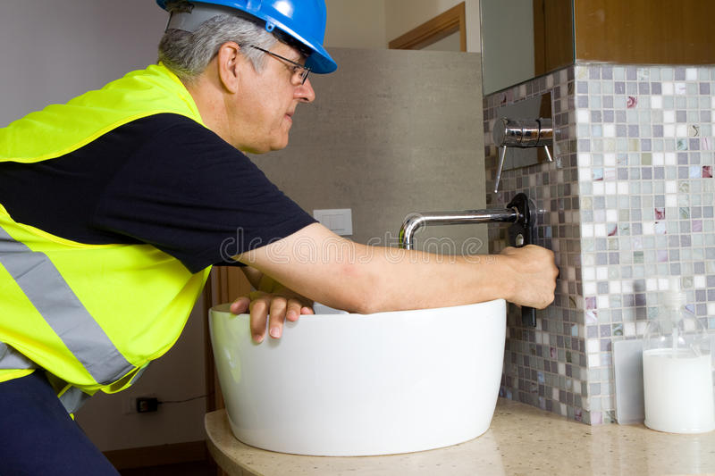 Plumber at work. Fitting new plumbing in a building stock images