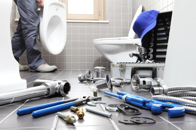 Hands plumber at work in a bathroom, plumbing repair service, as. Plumber at work in a bathroom, plumbing repair service, assemble and install concept royalty free stock photos