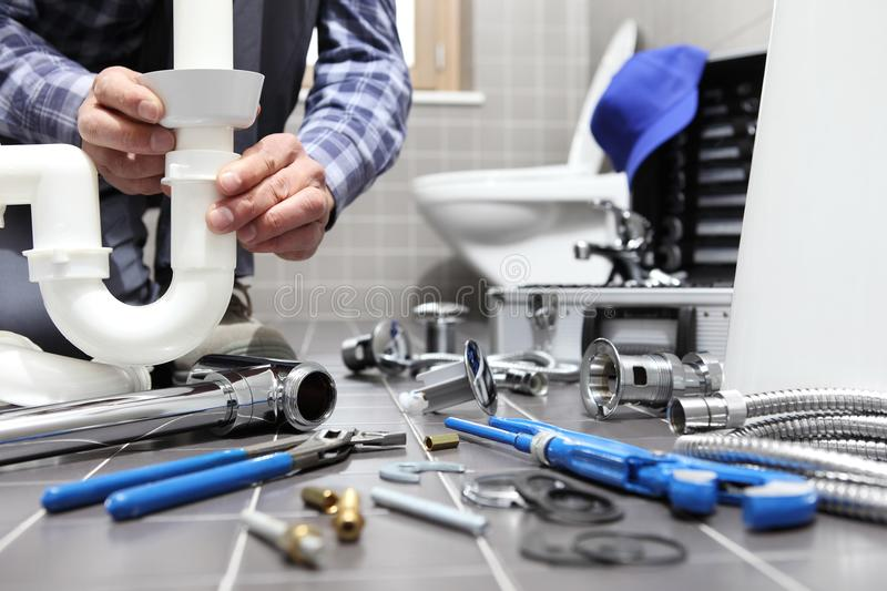 Plumber at work in a bathroom, plumbing repair service, assemble. And install concept stock photos