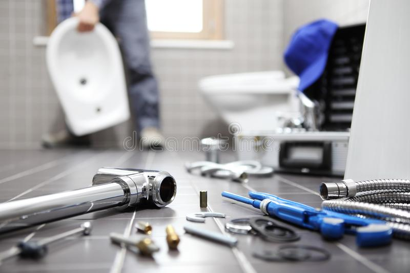 Plumber at work in a bathroom, plumbing repair service, assemble. And install concept royalty free stock images