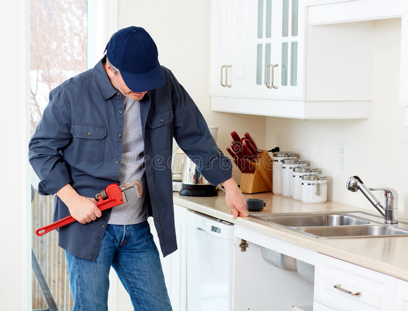Plumber worker. Professional plumber doing renovation in kitchen home stock images