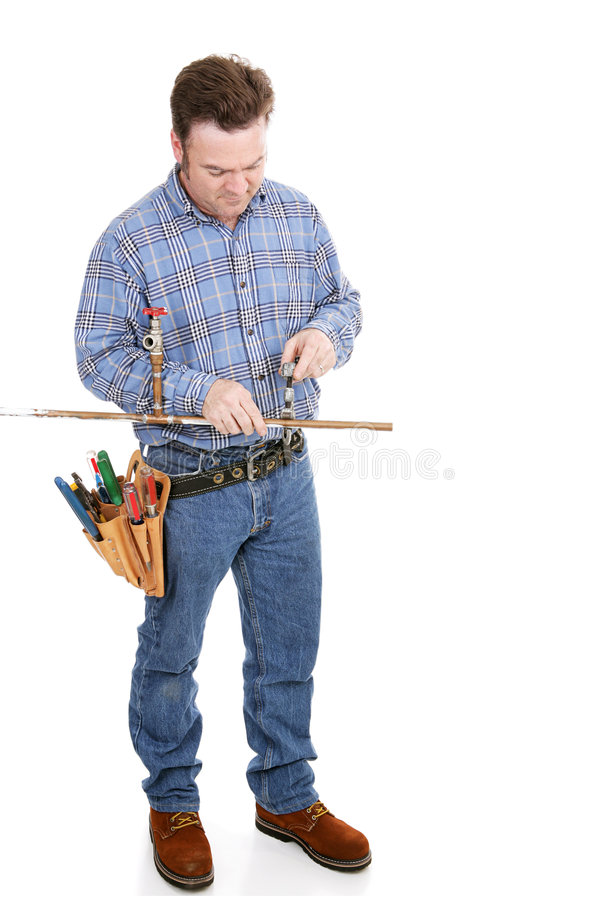 Plumber Working Full Body. Full body view of a plumber working on copper pipe. Isolated on white royalty free stock photo