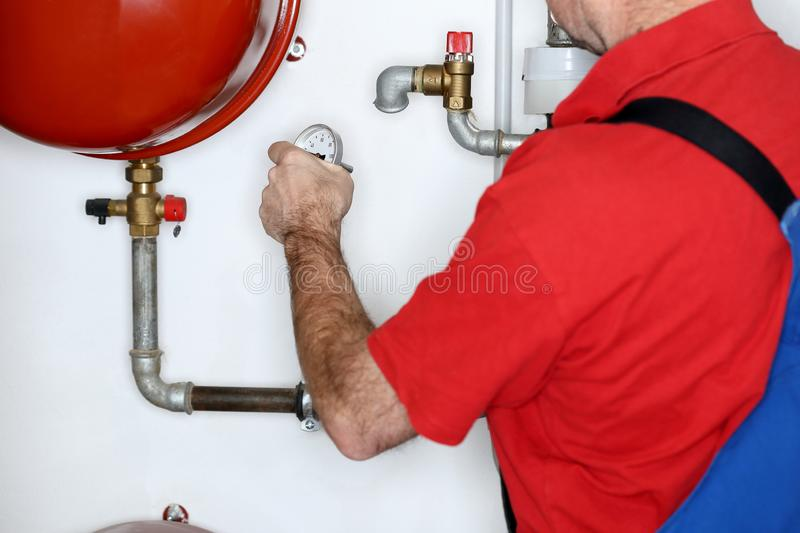 Plumber is working in a heating room. With thermometer in hand stock image
