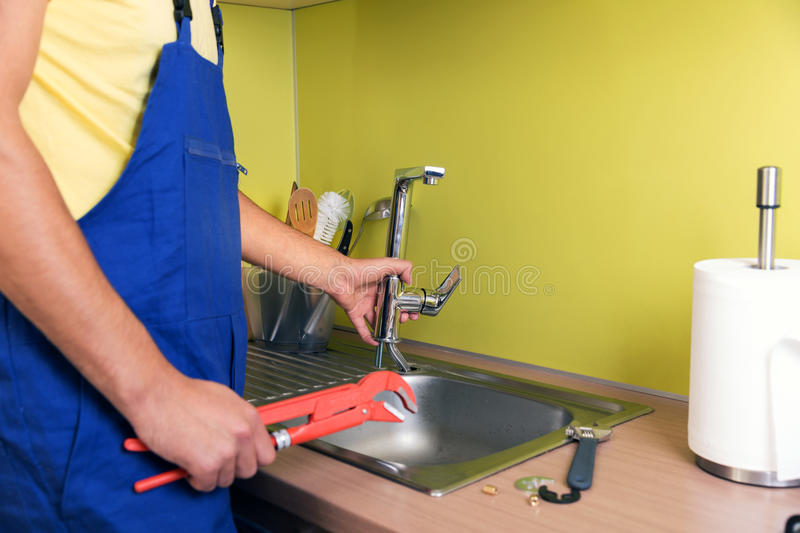 Plumber working in kitchen, repairing faucet royalty free stock photo