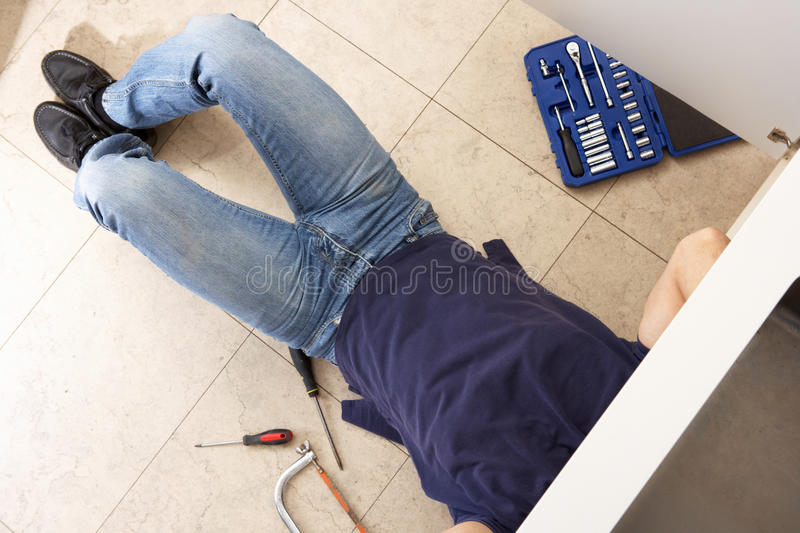 Plumber Working On Sink. In Kitchen royalty free stock photos