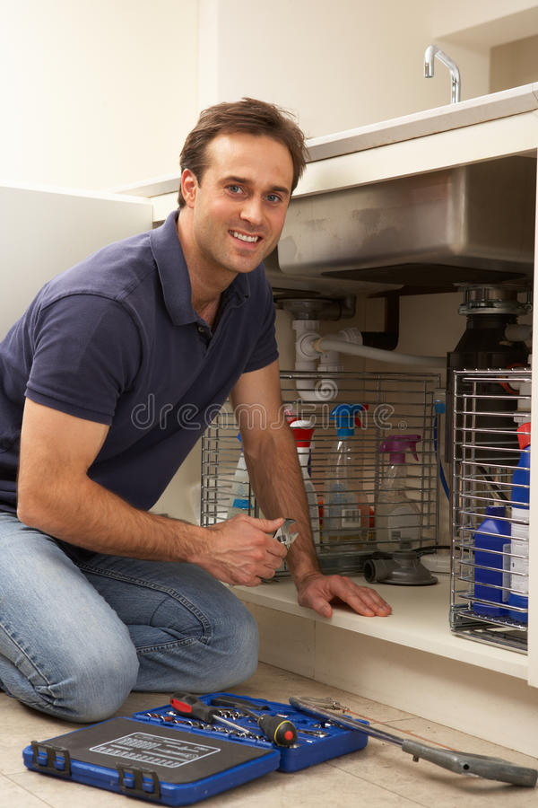 Plumber Working On Sink. In Kitchen royalty free stock photo