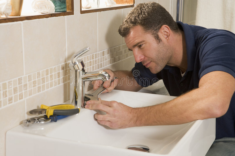 Plumber working on sink. With tools stock images