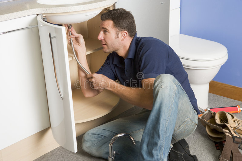 Plumber working on sink. With tools royalty free stock images