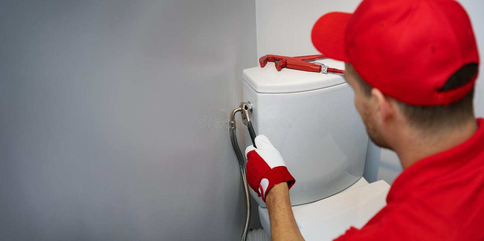 Plumber working in toilet installing water pipe to wc tank copy space royalty free stock photography