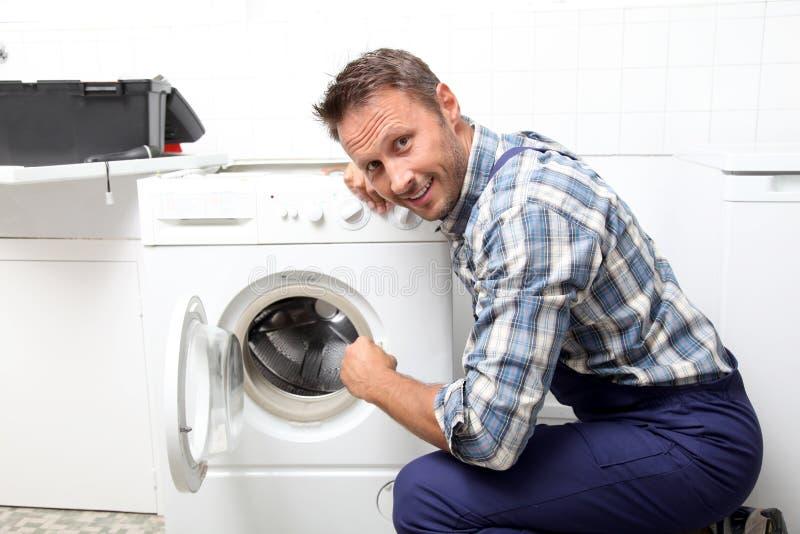 Plumber working on washing machine royalty free stock photos