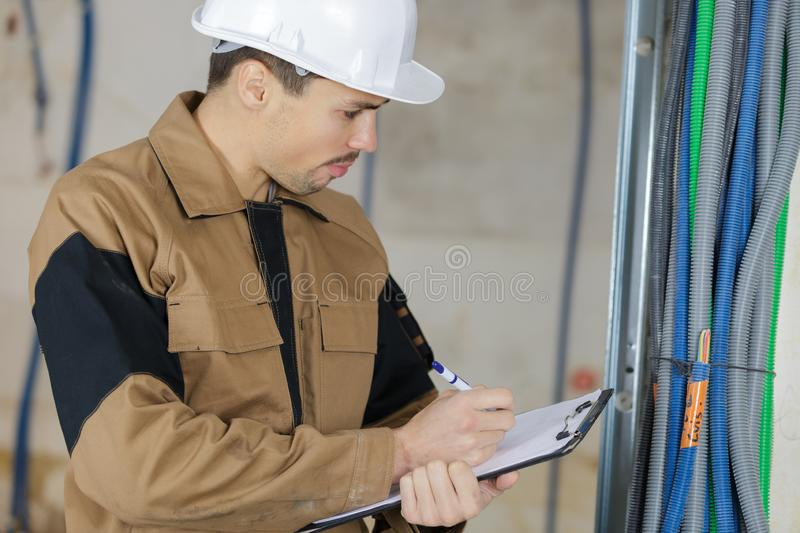 Plumber working with water pipes in boiler room stock photography