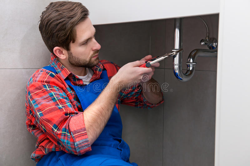 Plumber working. Young plumber is repairing a sink at the bathroom stock images