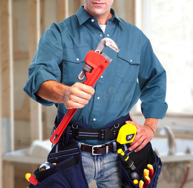 Plumber with wrench. Hand of plumber with wrench over blue construction background stock image