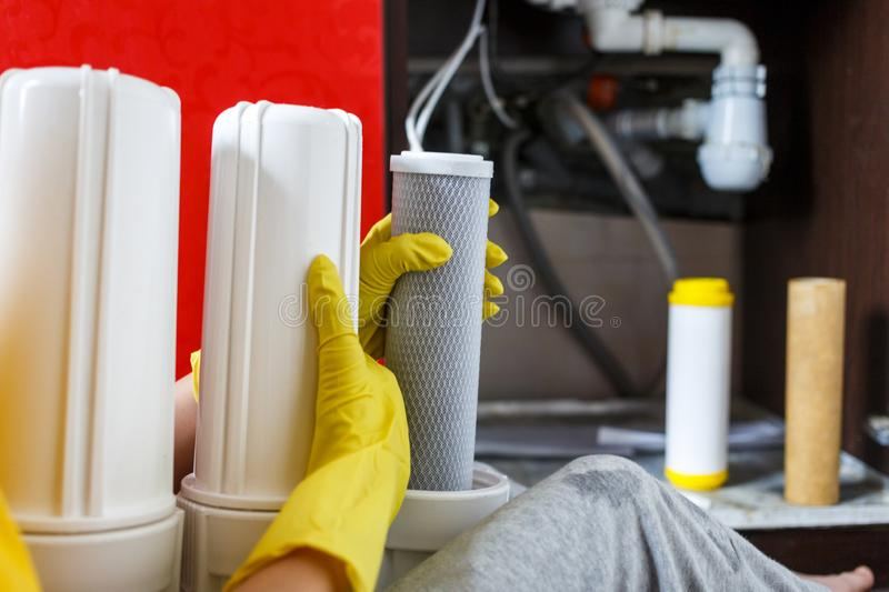 Plumber in yellow household gloves changes water filters. Repairman installing water filter cartridges in kitchen. Drinkable water filtration system in the royalty free stock photos