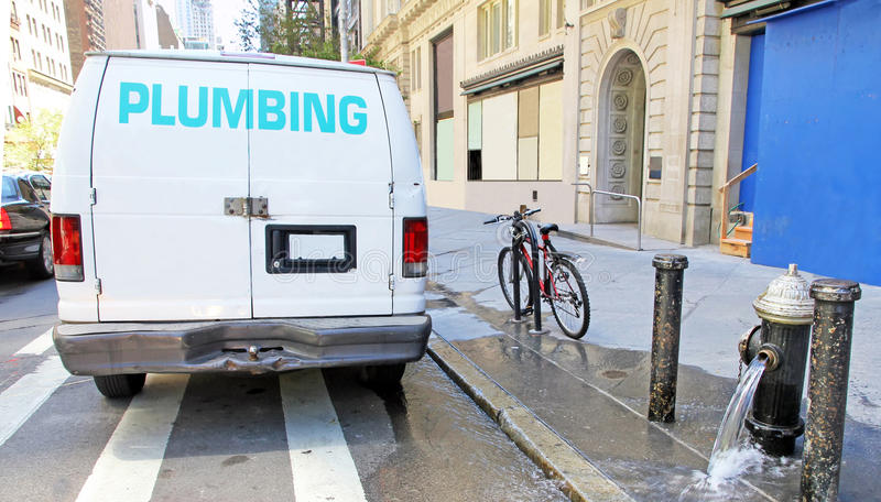 Plumbing Emergency. Water pipe bursts on 57th Street in NYC, flooded the street with water. A plumbing van arrived to repair the broken pipe royalty free stock image
