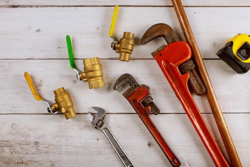Plumbing gate ball vales, fixtures on monkey wrench and tape measure on wooden board. Plumbing gate ball vales, fixtures and monkey wrench and tape measure on stock images