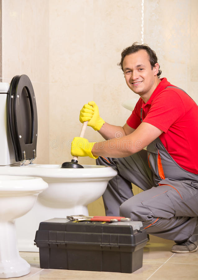Plumbing. Plumber is cleaning sink with plunger in the bathroom royalty free stock image