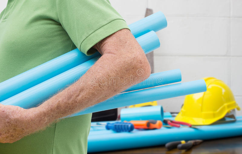 Plumbing Service. Worker Carrying Blue Pipe With Plumbing Tools Background royalty free stock photo
