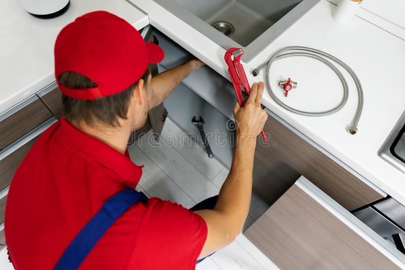 Plumbing services - plumber working in domestic kitchen, repairing sink pipes stock photos