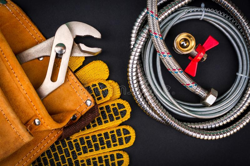 Plumbing tools in the bag for connecting water hoses on black background. Plumbing tools in the bag for connecting water hoses on dark black background royalty free stock images
