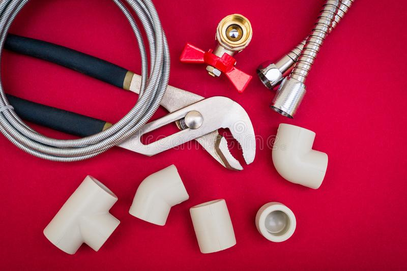 Plumbing tools for connecting water hoses on red background. Plumbing tools, cable for connecting water hoses on red background stock images