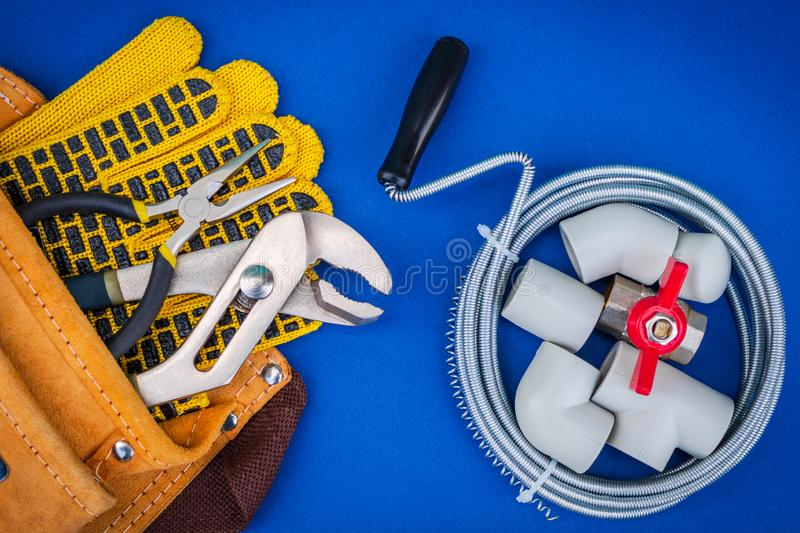 Plumbing tools and gloves for connecting water hoses on blue background. Plumbing tools, cable and gloves in bag for connecting water hoses on blue background royalty free stock image