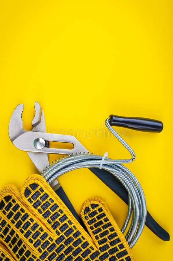 Plumbing tools and gloves for connecting water hoses on yellow background. Plumbing tools, cable and gloves for connecting water hoses on yellow background stock photo