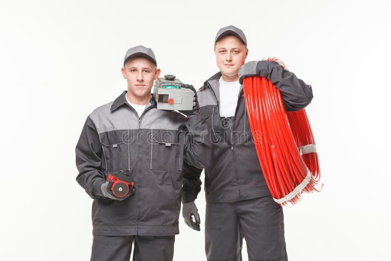 Plumbing tools two man. Plumbing tools two men white background studio royalty free stock photography