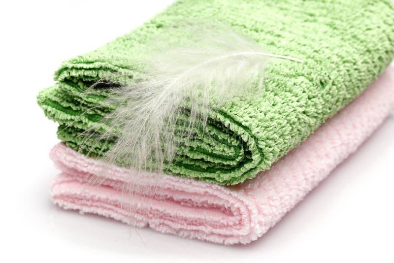 Plume blanche sur le rose et la serviette colorée verte photographie stock